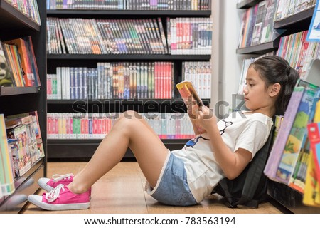 Children's education lifestyle learning concept with school girl kid reading book sitting on the floor of bookstore or library reading cartoon paperback among  bookshelf aisle
