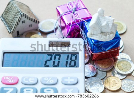 New year concepts,2018 Number on calculator display,house model and gift place on coins. #783602266