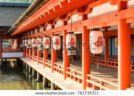 "Paper lanterns with characters meaning ""votive lanterns"" hanging from wooden eaves of a walkway at Itsukushima Shinto shrine on Miyajima, Hiroshima, Japan. #783739351"