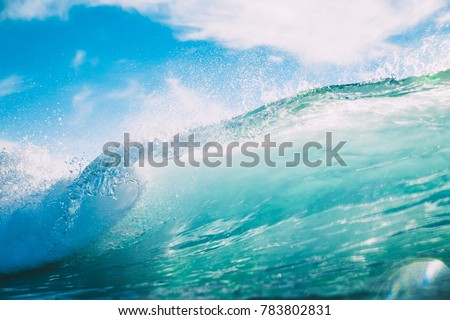 Blue wave in ocean. Breaking wave and sun light #783802831