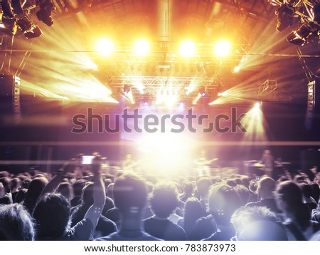 Concert venue crowded with ecstatic fans looking at the main stage lit in gold. #783873973