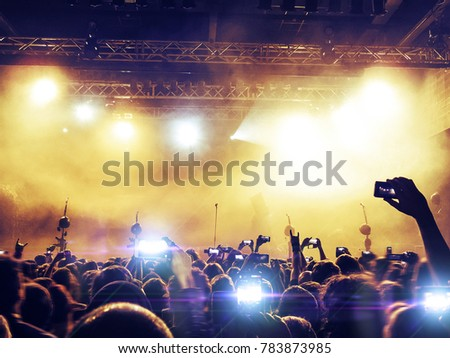Concert venue crowded with ecstatic fans looking at the main stage lit in gold. #783873985