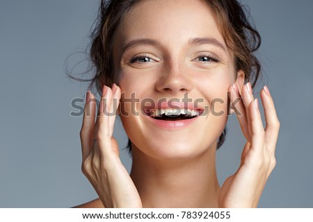 Image with beautiful brunette girl touching her face on grey background. Close up. Beauty & Skin care concept #783924055
