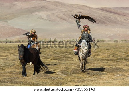 SAGSAY, MONGOLIA - SEP 28, 2017: Eagle Hunters traditional clothing, while hunting to the hare holding a golden eagles on his arms in desert mountain of Western Mongolia. #783965143