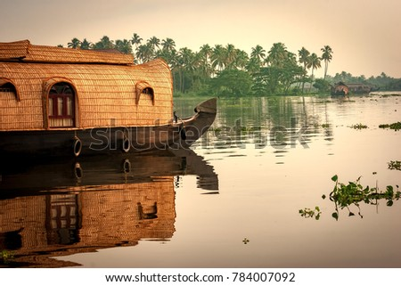Alleppey, Kerala, India - October 15, 2007 : Backwater tourism is an important tourism attraction in this city of Kerala; Houseboats are seen all over the backwater streams carrying tourists  #784007092