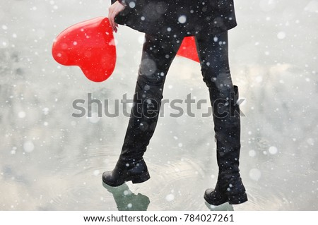 beautiful young girl with a balloon in the shape of a heart on the background of a frozen river or pond. Winter, February 14, Lovers' Day #784027261