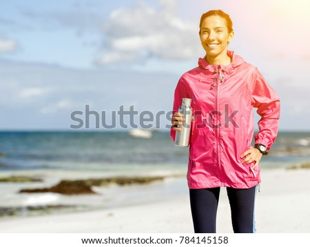 Beautiful girl in sport clothes drinking water after workout on the beach #784145158