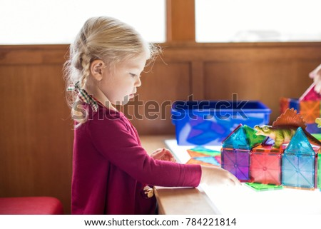 Preschool aged little girl playing at light table building with magnetic tiles #784221814