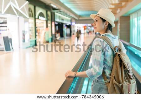beautiful Asian woman walking around airport. looking window shopping of the duty free shop on the escalator conveyor belt. #784345006