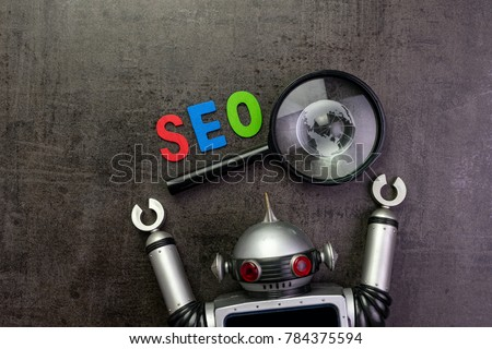 SEO Search engine optimization concept with alphabet abbreviation SEO and globe on magnifying glass and vintage robot. #784375594