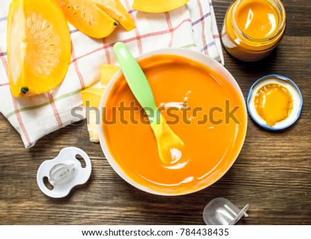 Baby food. Baby puree from fresh pumpkin. On a wooden table. #784438435