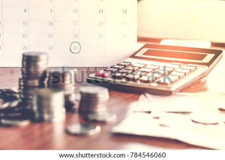 debt collection and tax season concept with deadline calendar remind note,coins,banks,calculator on table, background ,time to pay concept  Royalty-Free Stock Photo #784546060