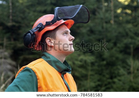Portrait of young lumberjack with protective helmet. #784581583