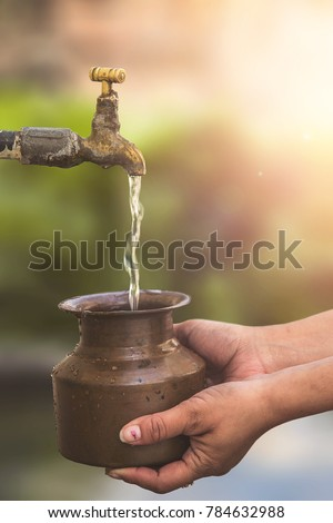 Indian women filling a pot also known as loto with water from a standpipe in a rural Indian village #784632988