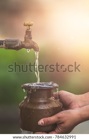 Indian women filling a pot also known as loto with water from a standpipe in a rural Indian village #784632991
