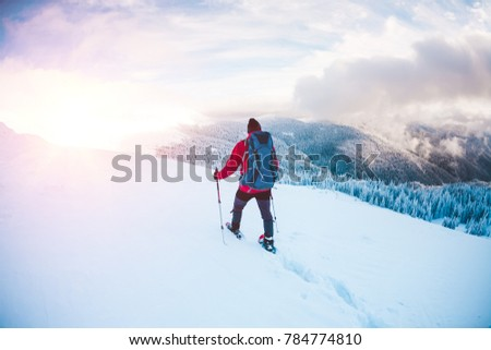 A man in snowshoes and trekking sticks in the mountains. Winter trip. Climbing of a climber against a beautiful sky with clouds. Active lifestyle. Climbing the mountain through the snow. #784774810