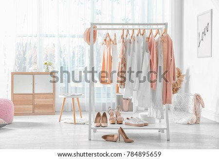 Collection of clothes hanging on rack in dressing room Royalty-Free Stock Photo #784895659