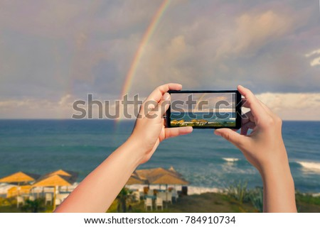 Female taking picture on mobile phone of double rainbow over ocean and tropical beach with umbrellas chairs and tables. Top view. Landscape on  smartphone