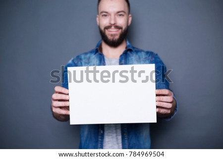 Young smiling man in a denim shirt shows a white sheet of paper in the camera on a gray background. Area for advertising. #784969504
