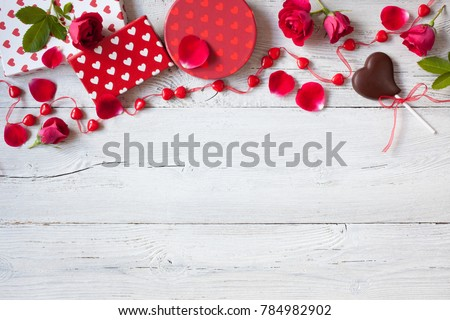 Roses and red hearts on a wooden background and gifts in boxes #784982902