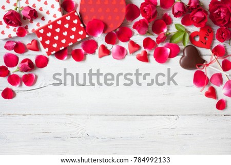 Roses and red hearts on a wooden background and gifts in boxes #784992133