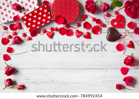 Roses and red hearts on a wooden background and gifts in boxes #784992454
