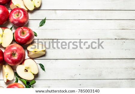 Fresh red apples with leaves. On a white wooden background.