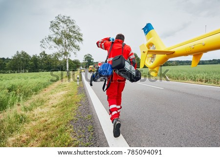 Doctor with defibrillator and other equipment running from helicopter. Teams of the Emergency medical service are responding to an traffic accident. Royalty-Free Stock Photo #785094091
