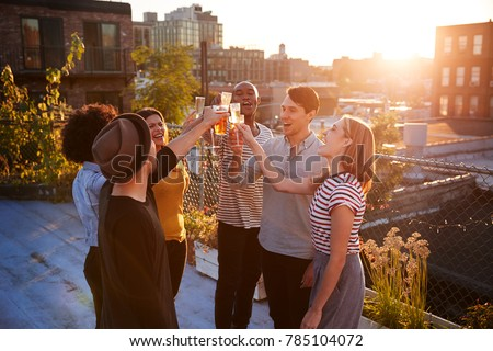 Friends make a toast at a rooftop party, backlit by sunlight #785104072
