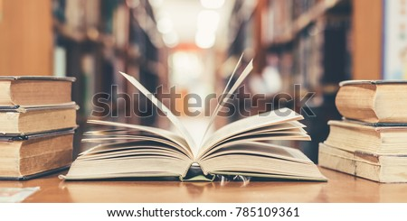 Book in library with old open textbook, stack piles of literature text archive on reading desk, and aisle of bookshelves in school study class room background for academic education learning concept #785109361