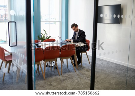 Young businessman working alone in a boardroom #785150662