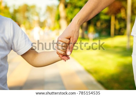 Cropped close up of a boy and grandmother holding hands. CLose up of hands of a child and parent on the walk at the local park in summer family love bonding children parenting family weekend leisure Royalty-Free Stock Photo #785154535