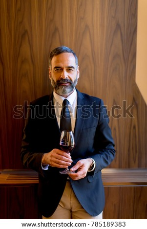 Portrait of handsome man with glass of red wine #785189383