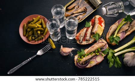 Vodka and a set of sandwiches with sprats, and caviar, onion and parsley, on a wooden background. Top view. Copy space. #785222515