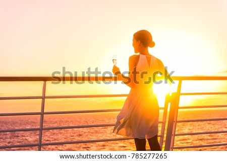 Luxury cruise ship travel elegant woman drinking glass of champagne enjoying watching sunset from boat deck over ocean in Europe destination vacation. Cruising sailing away on holiday. #785277265