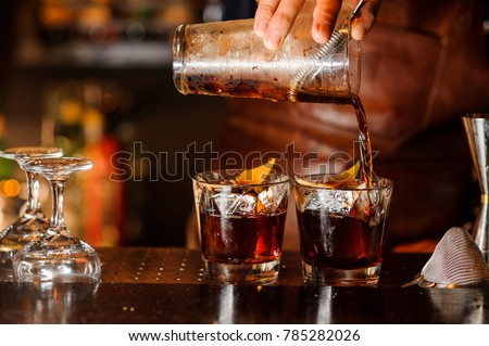 Bartender pouring fresh alcoholic drink into the glasses with ice cubes on the bar counter #785282026