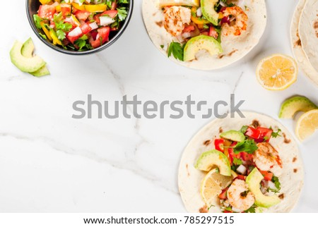 Seafood. Mexican food. Tortilla tacos with traditional homemade salsa salad, parsley, fresh lemon, avocado and grilled shrimp pawns. On a white marble background. Top view copy space #785297515
