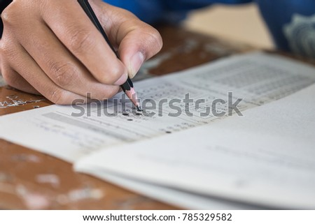 Front view Asian Students, undergraduate holding pencil writing on multiple-choice quizzespaper answer sheet and sitting on old lecture chair in final exam classroom, Education  literacy concept. #785329582