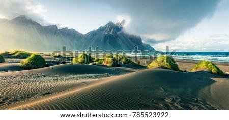 Black sand dunes on the Stokksnes headland on southeastern Icelandic coast with Vestrahorn (Batman Mountain). Picturesque summer panorama of Iceland, Europe. Instagram filter toned. #785523922