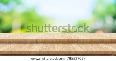 Empty step wood table top food stand with blur green park tree background bokeh light,Mock up for display or montage of product,Banner for advertise on online media,nature business presentation #785539087