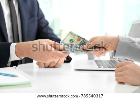 Businessman taking bribe from woman at table indoors #785540317