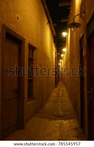 A small narrow way through a street with lights #785545957