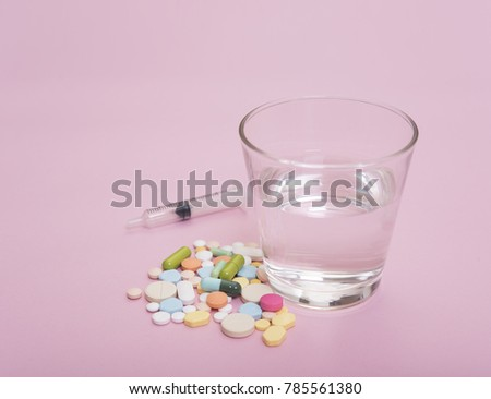 colorful medicine and glass of water on pink background. #785561380