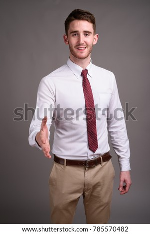 Studio shot of young handsome businessman wearing white shirt and red tie against gray background #785570482