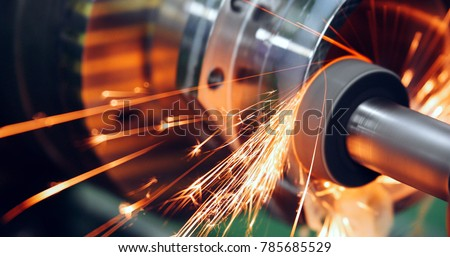 sparks flying while machine griding and finishing metal #785685529