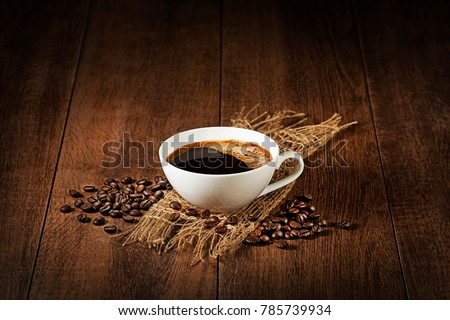 Coffee cup with beans on wooden table. Copyspace for your text #785739934