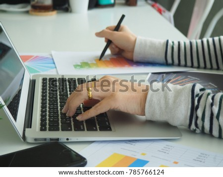 businesswomen using laptop analyzing marketing strategy with statistic graph and notebook on the table. #785766124