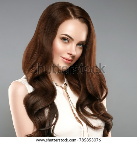 Beautiful shine hair woman with manicure nails hand. Brunette with long hair and healthy skin over gray background. Studio shot. #785853076