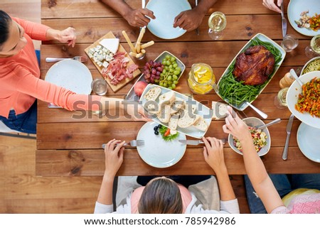 thanksgiving day, eating and leisure concept - group of people having dinner at table with food #785942986