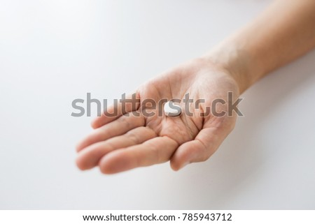 medicine, nutritional supplements and people concept - close up of hand holding pill in shape of heart #785943712